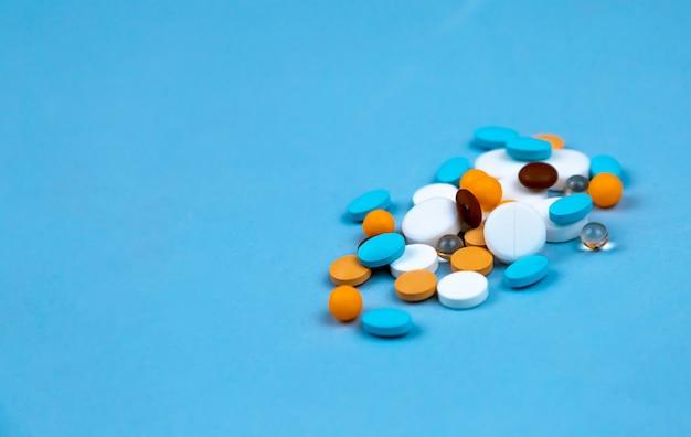 Pilules multicolores sur un gros plan de fond bleu,