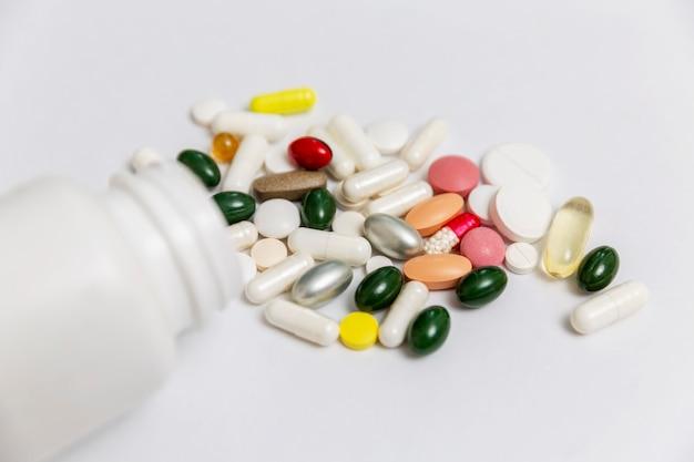 Pilules multicolores renversées d'une bouteille blanche sur une table. médicament. fermer. espace pour le texte.