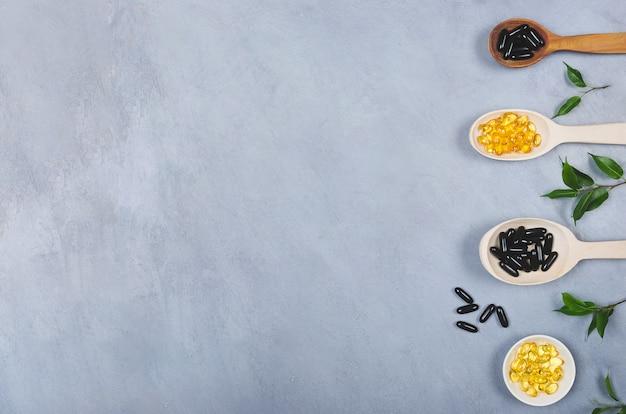 Pilules noires et jaunes et cuillère en bois sur fond gris