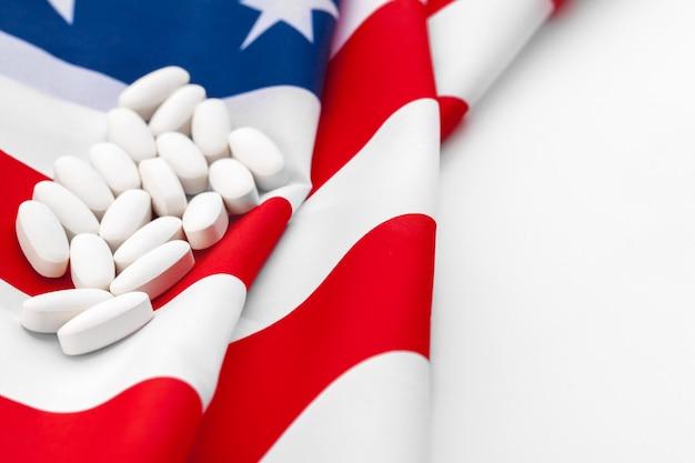 Pilules de prescription blanches sur le drapeau des états-unis