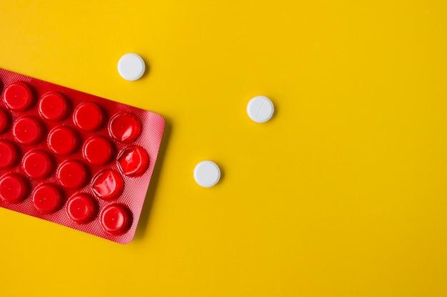 Pilules rondes blanches dans un emballage rouge sur jaune avec espace de copie