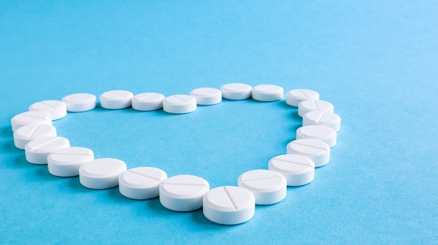 Pilules rondes blanches disposées en forme de coeur sur fond bleu.