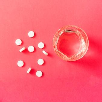 Pilules rondes blanches et verre d'eau sur fond rouge