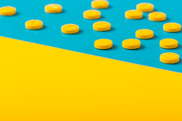 Pilules rondes jaunes sur deux arrière-plans colorés