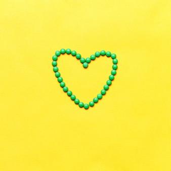 Pilules rondes vertes comprimés en forme de cœur sur fond jaune