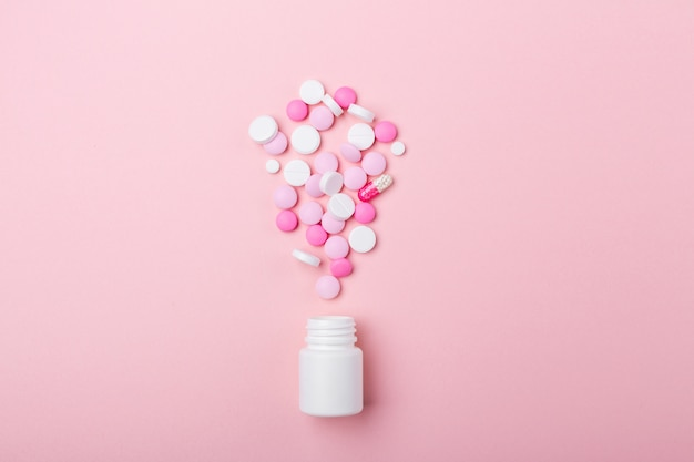 Pilules roses et blanches sur fond rose bouteille en plastique tas de comprimés et de pilules de médicaments variés. soins de santé.