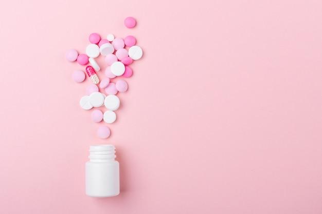 Pilules roses et blanches sur rose