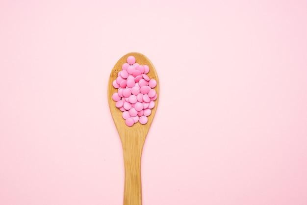 Pilules roses en cuillère isolé médecine pharmacie de fond