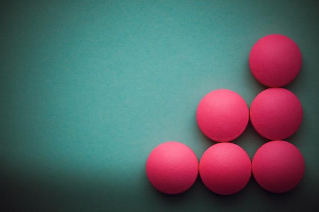 Pilules roses disposées sur un fond vert.