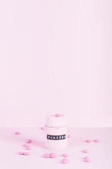 Pilules roses entourées de placebo bouteille fermée sur fond rose