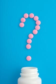 Pilules roses sur fond bleu. vue de dessus. point d'interrogation.
