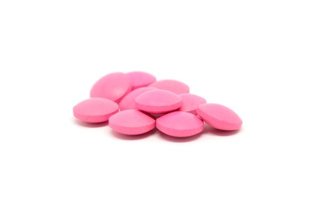 Pilules roses isolés sur fond blanc.