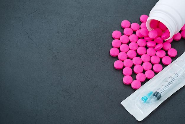 Les pilules roses sont dispersées dans un bocal sur fond gris avec une seringue.