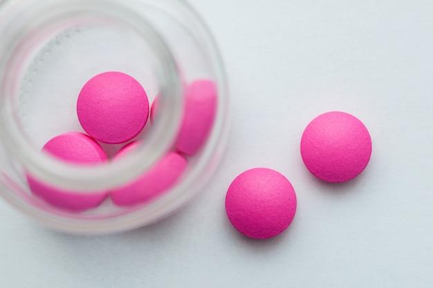 Les pilules roses sont versées à partir d'un bocal en verre sur un fond blanc. la vue du haut.