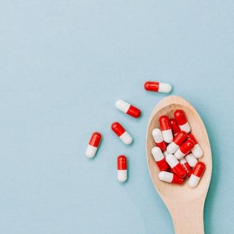 Pilules rouges et blanches sur la cuillère en bois