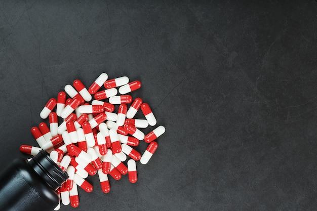 Pilules rouges et blanches d'un pot noir sur fond noir. espace libre