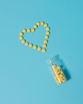 Pilules sédatives, valériane en forme de coeur sur fond bleu.