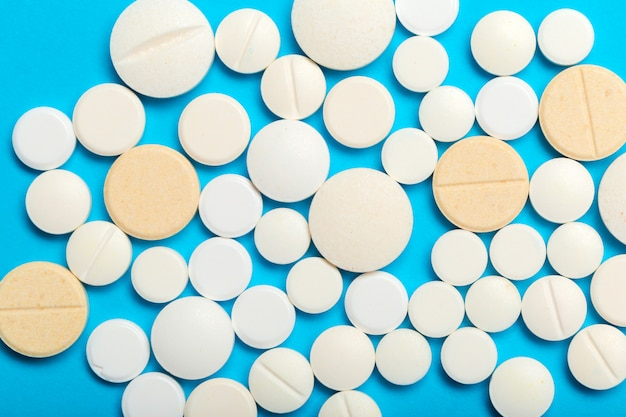 Les pilules sont dispersées sur le bleu