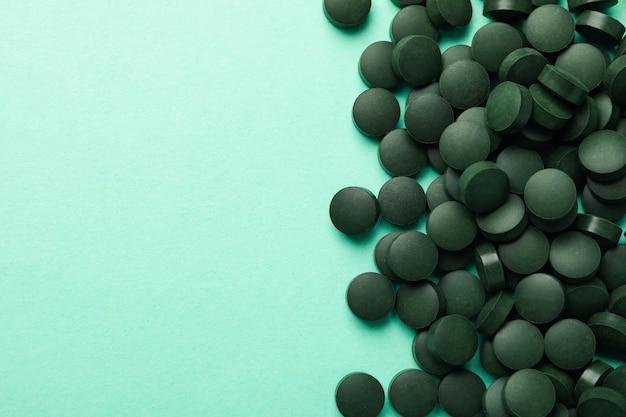 Pilules de spiruline sur fond de menthe, vue de dessus et espace pour le texte
