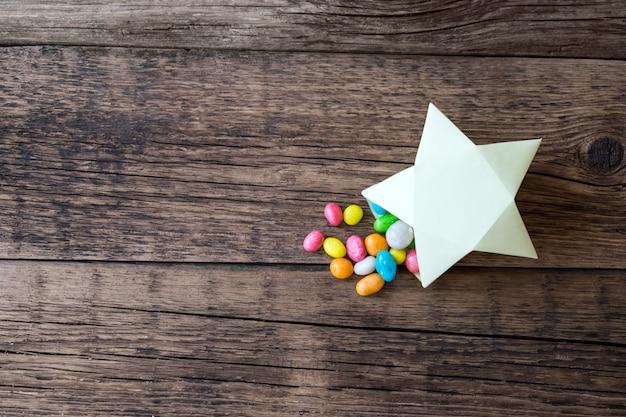 Pilules sucrées multicolores dans une boîte cadeau en papier
