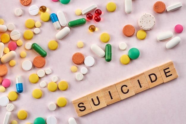 Pilules suicides sur fond blanc.