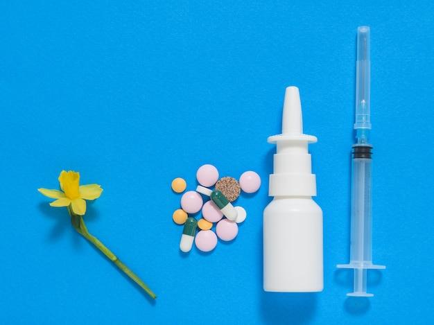 Pilules, vaporisateur nasal et une seringue avec une fleur sur fond bleu