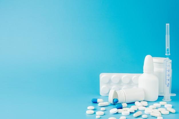 Pilules de variétés éparses, médicaments, stérilisation, bouteilles, thermomètre, seringue et caddie vide sur fond bleu