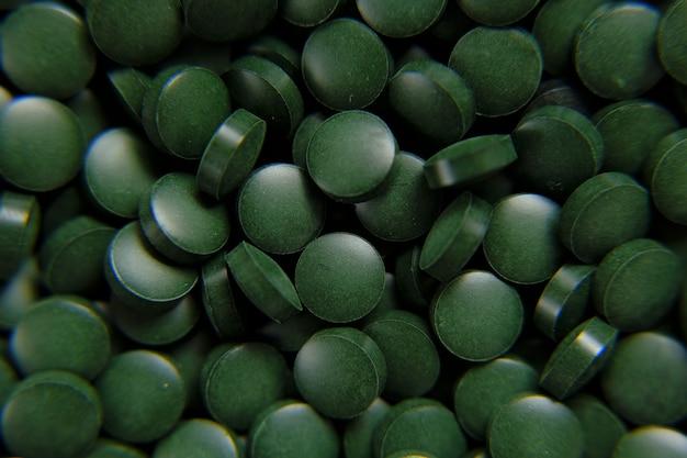 Pilules vertes de spiruline fond comprimés verts d'algues de spiruline