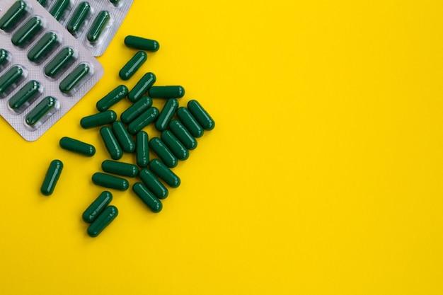 Pilules vertes sur la table jaune vue de dessus.