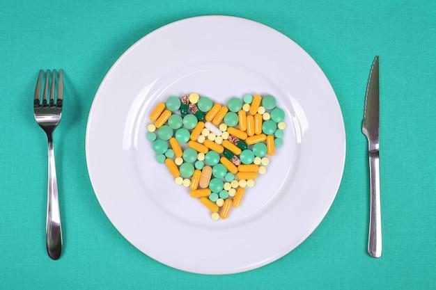 Les pilules et les vitamines sont disposées en forme de cœur sur une assiette blanche et des couverts sur une nappe turquoise.