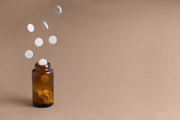 Les pilules volent dans un flacon sur un fond clair