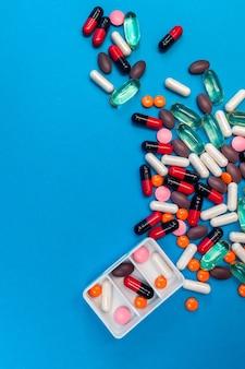 Pilulier avec pilules multicolores sur fond bleu