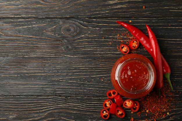 Piment et bocal en verre de sauce sur bois