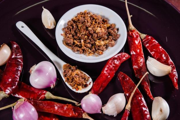 Piment de crevettes épicé sur cuillère et plat blanc