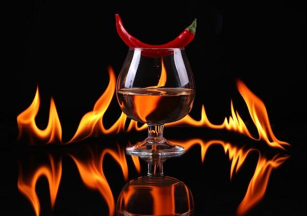 Piment dans un ballon de cognac avec un feu sur fond noir