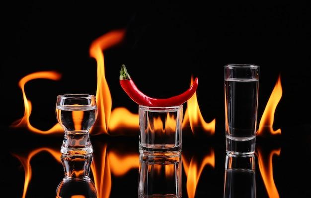 Piment fort dans un verre à shot avec un feu sur fond noir
