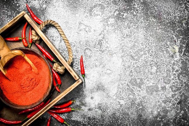 Piment frais moulu dans un bol sur un plateau sur un fond rustique