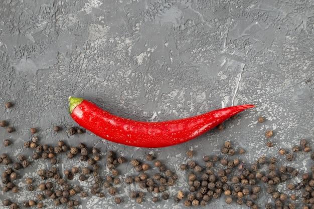 Piment et grains de poivre sur pierre