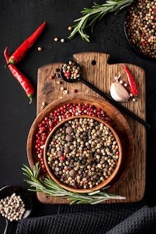 Piment noir et rouge dans des bols en bois, vue du dessus
