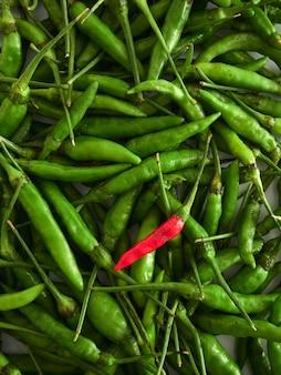 Un piment rouge aux piments verts