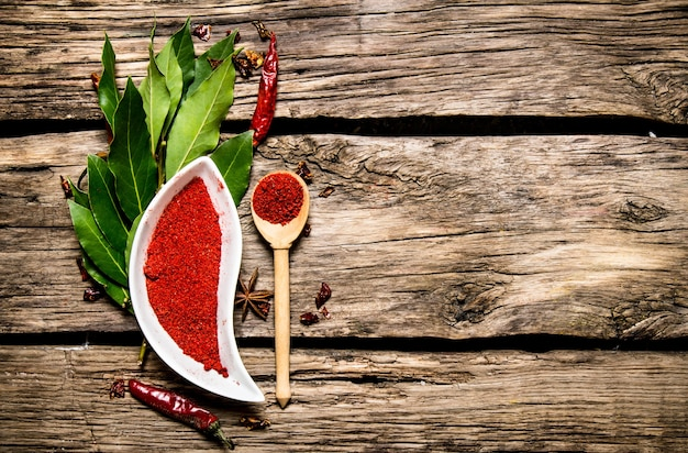 Piment rouge moulu et feuilles de laurier. sur fond de bois. espace libre pour le texte. vue de dessus