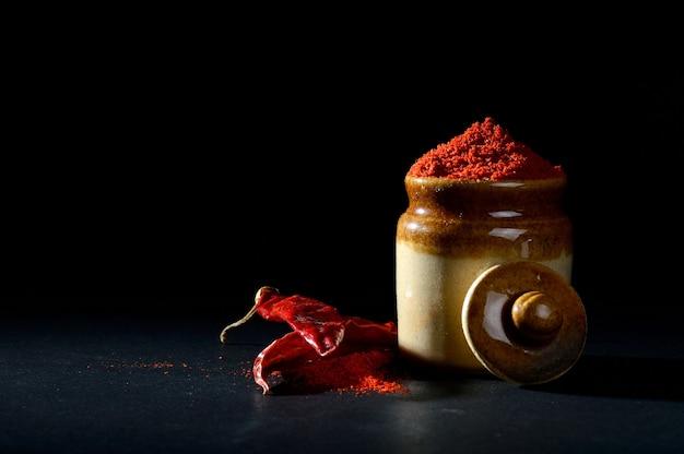 Piment rouge en poudre dans un pot en argile avec des piments rouges sur fond noir