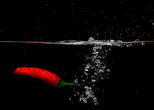 Piment rouge tombant avec des bulles dans l'eau sur fond noir