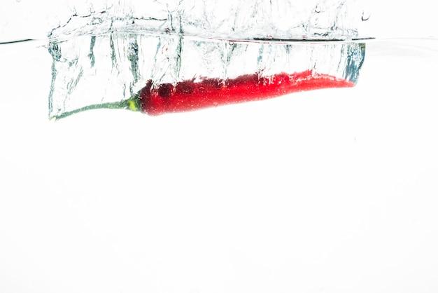 Piment rouge tombant dans l'eau sur fond blanc
