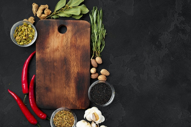 Piments et épices avec planche de bois sur fond noir