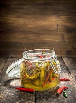 Piments forts marinés dans un bocal en verre sur table en bois.