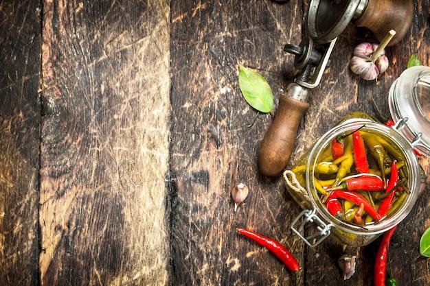 Piments forts marinés avec seamer sur table en bois.