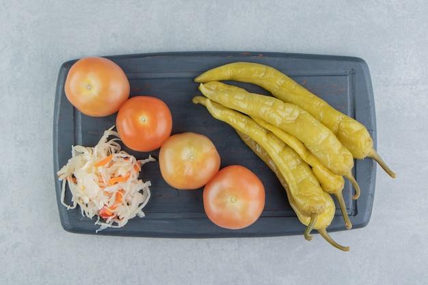 Piments forts, tomates et choucroute sur une planche sur la surface en marbre