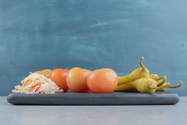 Piments forts, tomates et choucroute sur une planche