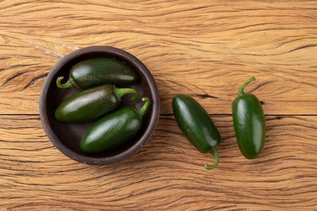 Piments jalapeno verts sur un bol sur une table en bois.